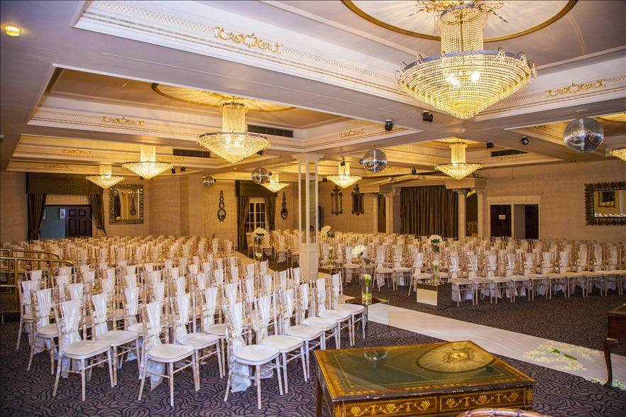 The white washed chiavari chairs used in the ballroom for the ceremony